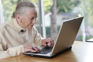 elderly lady typing on laptop